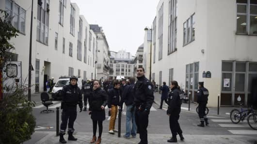Police forces gather in street outside the offices of Charlie Hebdo in Paris